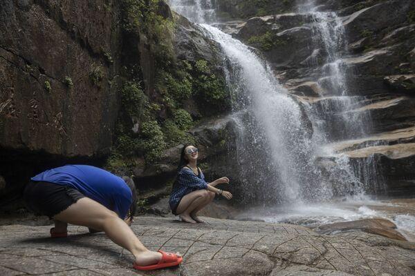 Žena pózuje u vodopádu ve Wu-i ve východní čínské provincii Fu-ťien - Sputnik Česká republika