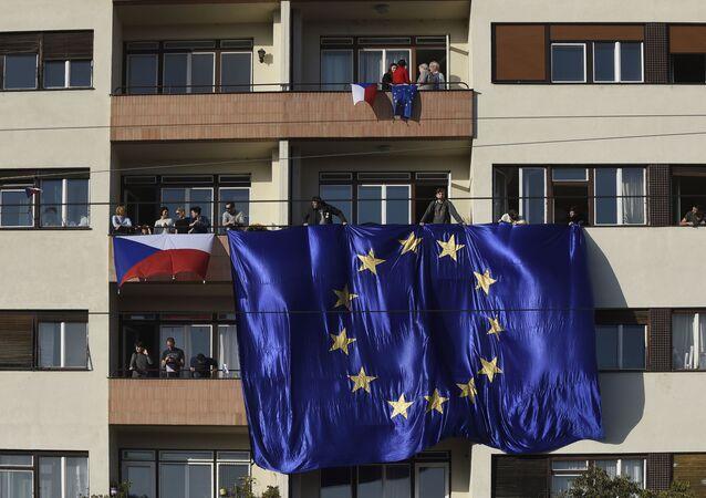 Lidé s českými a evropskými vlajkami na balkoně domu v Praze