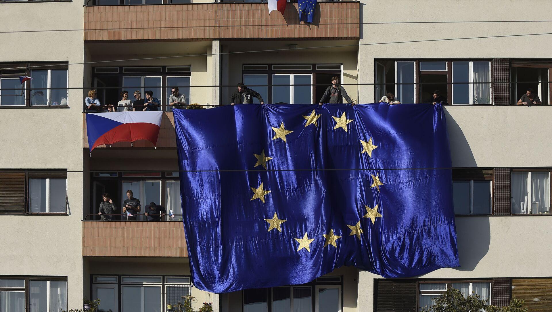 Lidé s českými a evropskými vlajkami na balkoně domu v Praze - Sputnik Česká republika, 1920, 30.03.2021