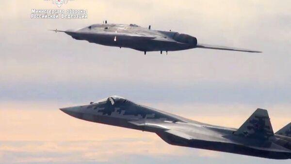 Společný let ruského letounu Su-57 a bezpilotního letounu Ochotnik (Lovec). Oba letounu jsou vybaveny technologií stealth, která snižuje viditelnost na nepřátelských radarech. - Sputnik Česká republika