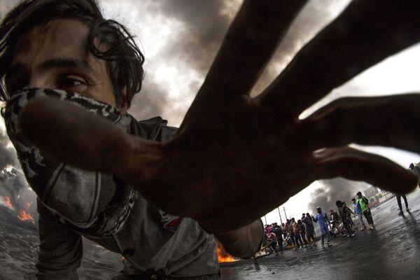 Účastník masových protestů ve městě Basra v Iráku - Sputnik Česká republika