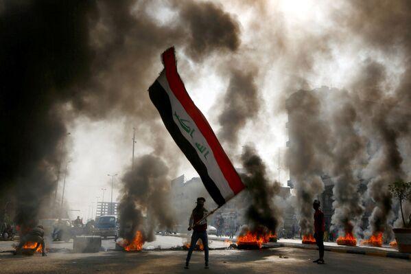 Protestující s iráckou vlajkou v ruce během protestu ve městě Nadžaf v Iráku - Sputnik Česká republika