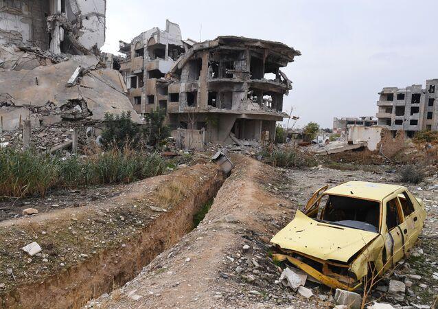 Zničené auto na pozadí trosek domů na předměstí Jobaru.