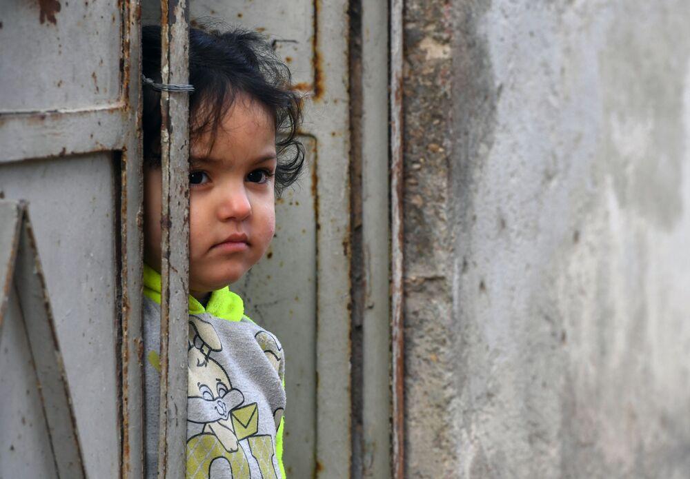 Dívka u dveří bytového domu ve městě Dúmá.