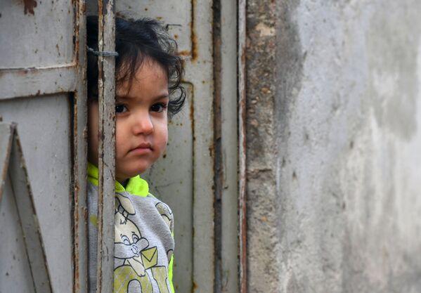 Dívka u dveří bytového domu ve městě Dúmá. - Sputnik Česká republika
