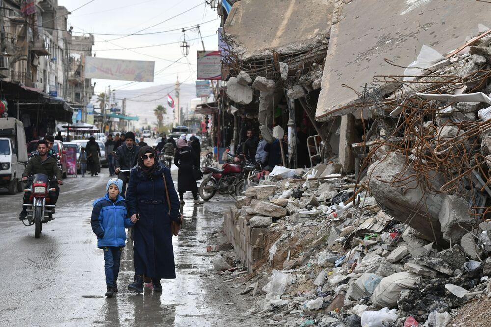 Žena s dítětem na ulici v Dúmě, Sýrie