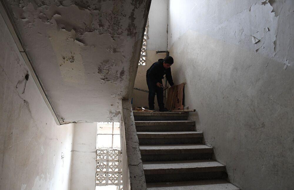 Chlapec na schodech v poškozené budově v Dúmě v Sýrii