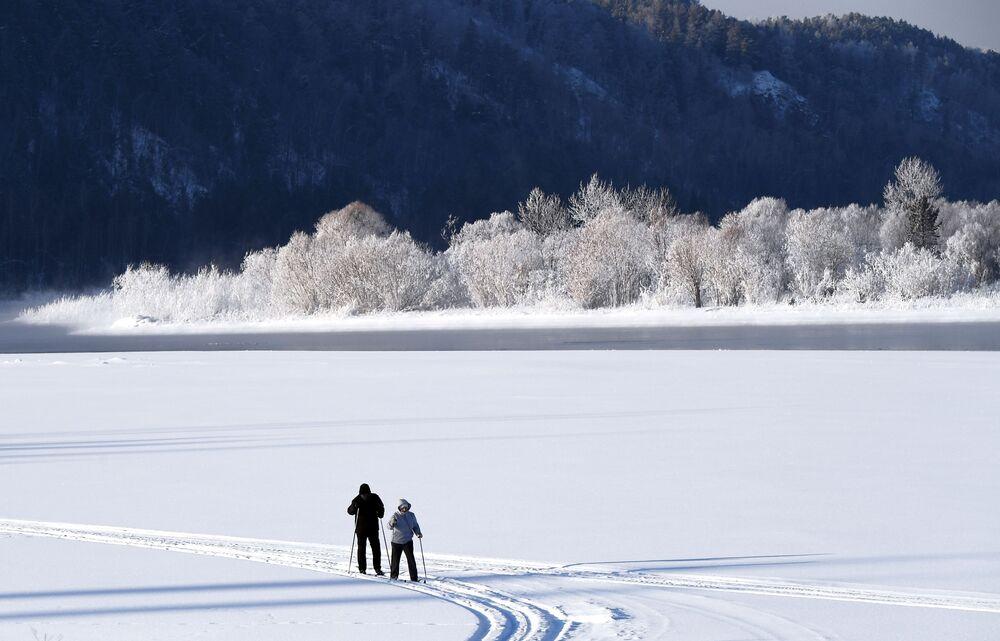 Lidé na lyžích na břehu řeky Jenisej
