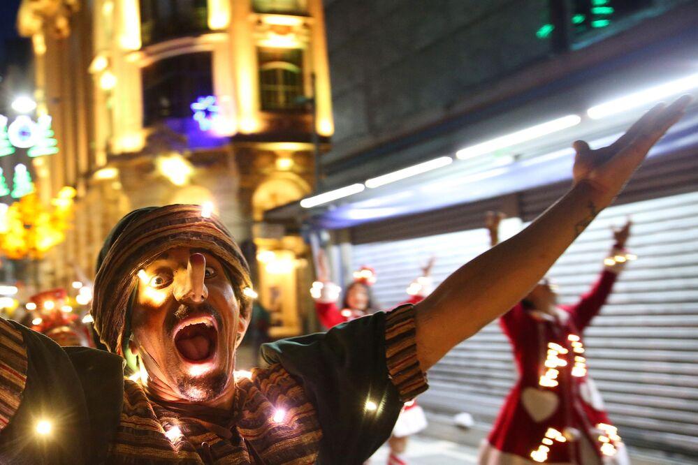 Muž v masce Pinocchia na vánočním karnevalu v brazilském São Paulu