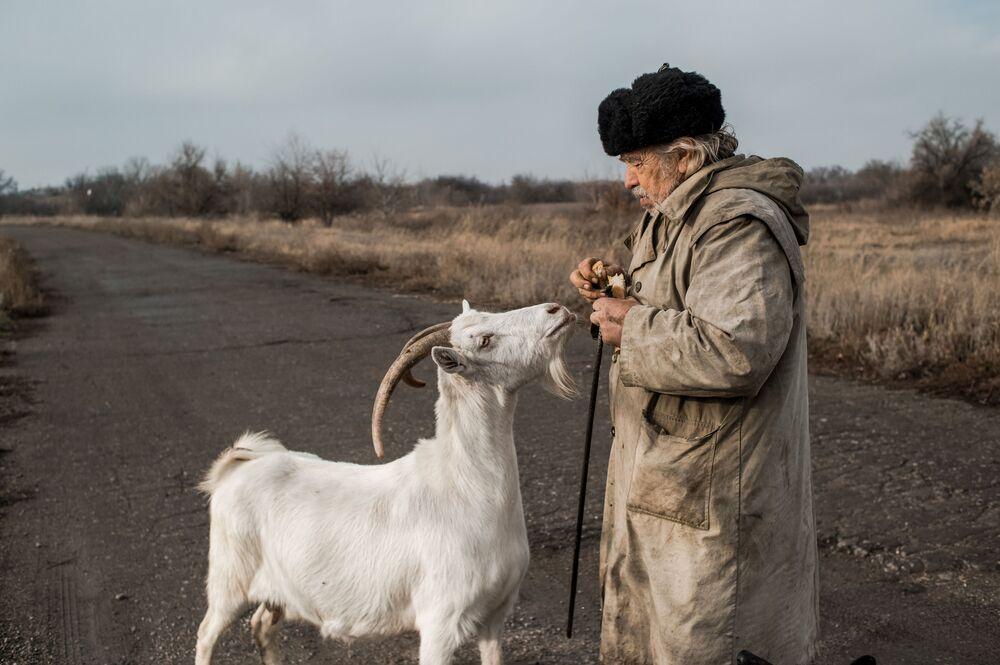 Starší muž s kozou ve vesnici Doněcké v Luhanské oblasti na Ukrajině