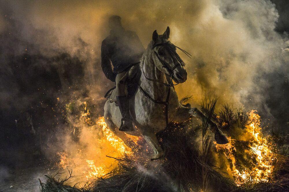 Jezdec projíždí ohněm během každoročního festivalu Las Luminarias ve španělské vesnici San Bartolome de Pinar