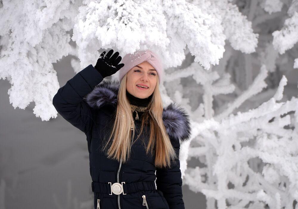 Žena pózuje v zasněženém lese na břehu Jeniseje