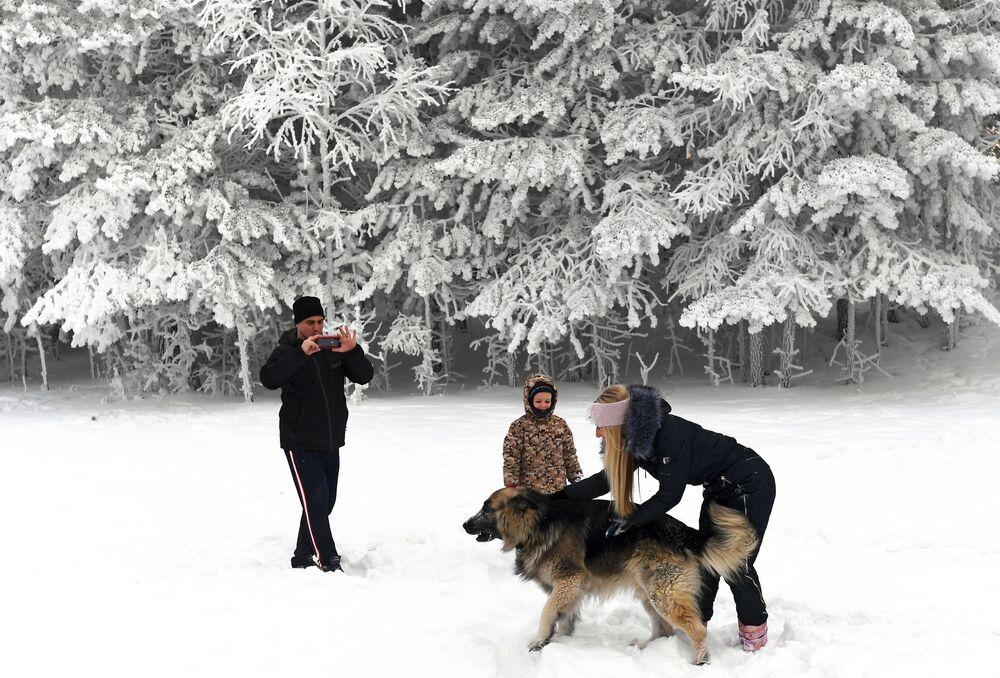 Lidé se fotí v zasněženém lese na břehu řeky Jenisej