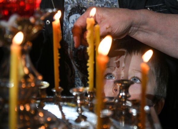 Dítě během vánoční bohoslužby v katedrále Krista Spasitele v Moskvě - Sputnik Česká republika