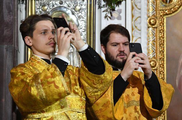 Pravoslavní věřící fotografují během vánoční bohoslužby v katedrále Krista Spasitele v Moskvě - Sputnik Česká republika