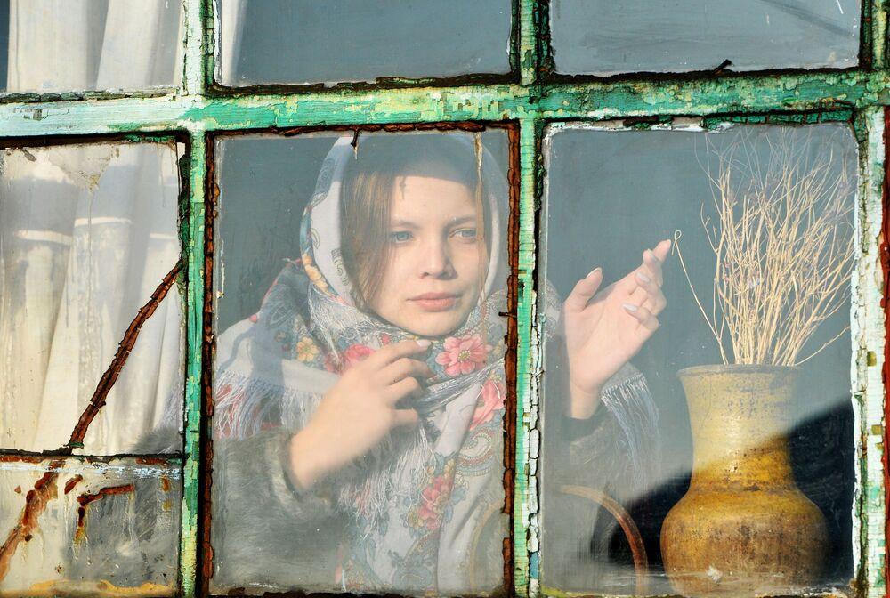 Dívka se dívá z okna během věštby v kozácké vesnici Černorechye Čeljabinské oblasti