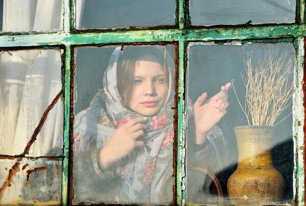 Dívka se dívá z okna během věštby v kozácké vesnici Černorechye Čeljabinské oblasti - Sputnik Česká republika