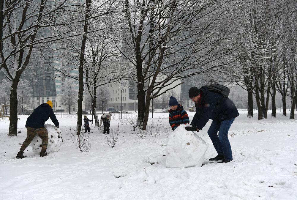 Dospělí staví s dětmi sněhuláky v Moskvě