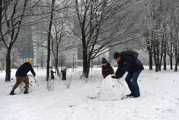 Dospělí staví s dětmi sněhuláky v Moskvě - Sputnik Česká republika