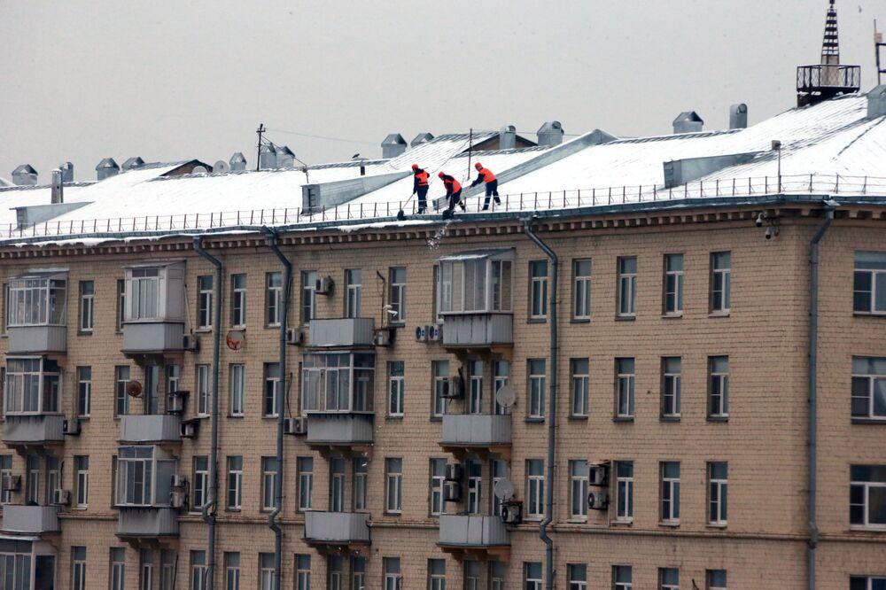 Pracovníci komunálních služeb odhrnují sníh ze střechy bytového domu v Moskvě