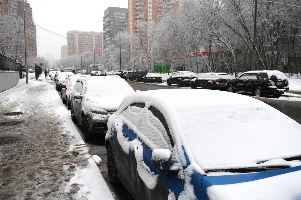 Zasněžená auta v jedné z ulic Moskvy