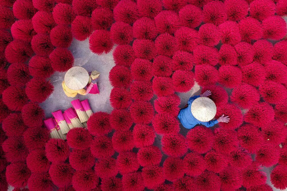 Vietnamské ženy shromažďují sušené vonné tyčinky na nádvoří na okraji Hanoje ve Vietnamu