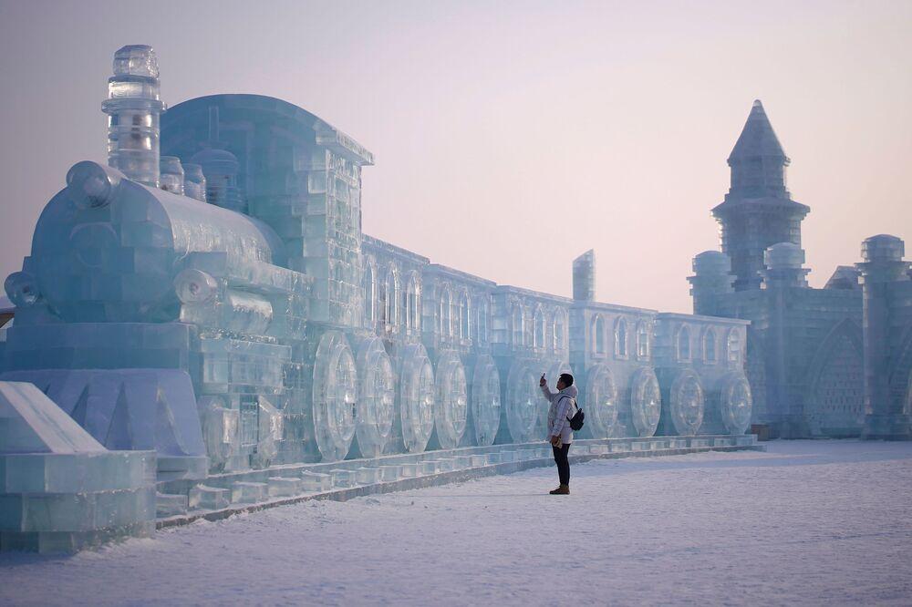 Muž u ledové sochy v čínském městě Charbin