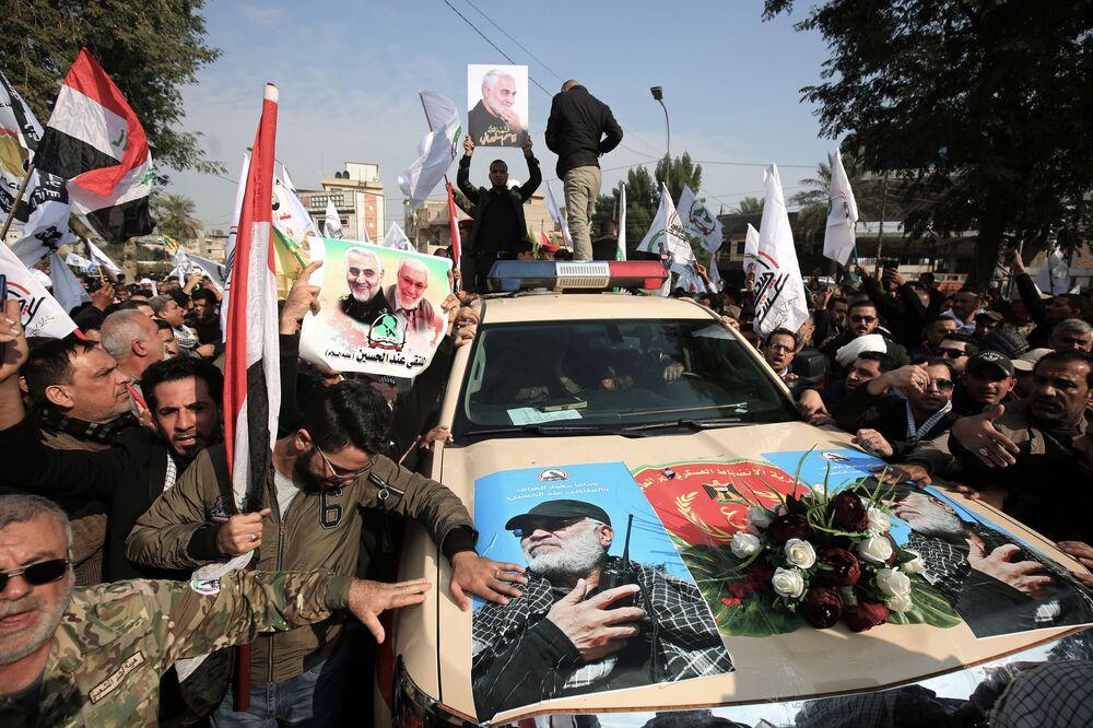 Auto s podobiznami iráckého vojáka Abu Mahdi al-Muhandise během pohřebního obřadu v Bagdádu