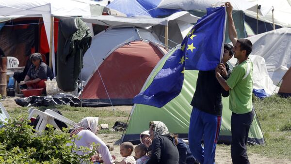 Migranti s vlajkou EU v táboře pro migranty a uprchlíky v Řecku - Sputnik Česká republika