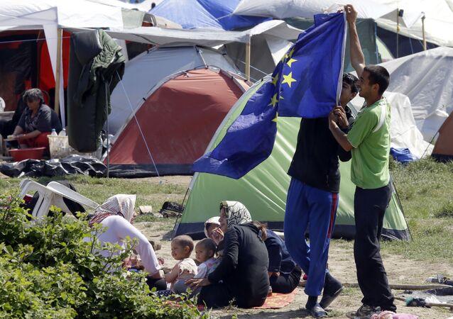 Migranti s vlajkou EU v táboře pro migranty a uprchlíky v Řecku