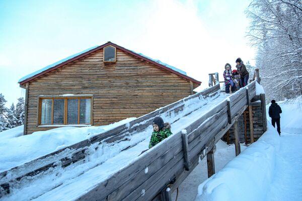 Děti jezdí z kopečku v Laponské přírodní biosférické rezervaci v Murmanské oblasti - Sputnik Česká republika