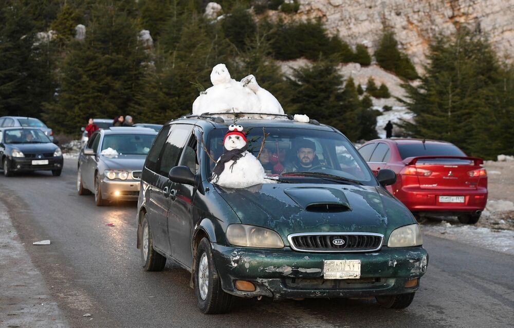 Syřané vozí na autech sníh z hor na pobřeží v horské části Latákíje