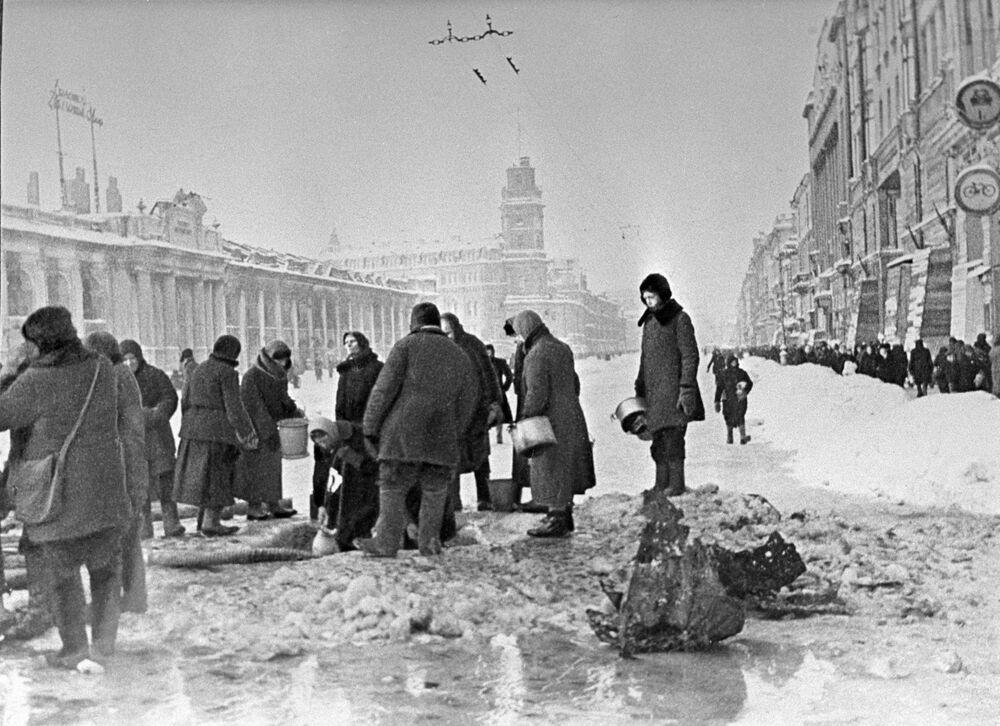 Obyvatelé Leningradu nabírají vodu, která se objevila v trhlinách asfaltu po dělostřeleckém ostřelování.