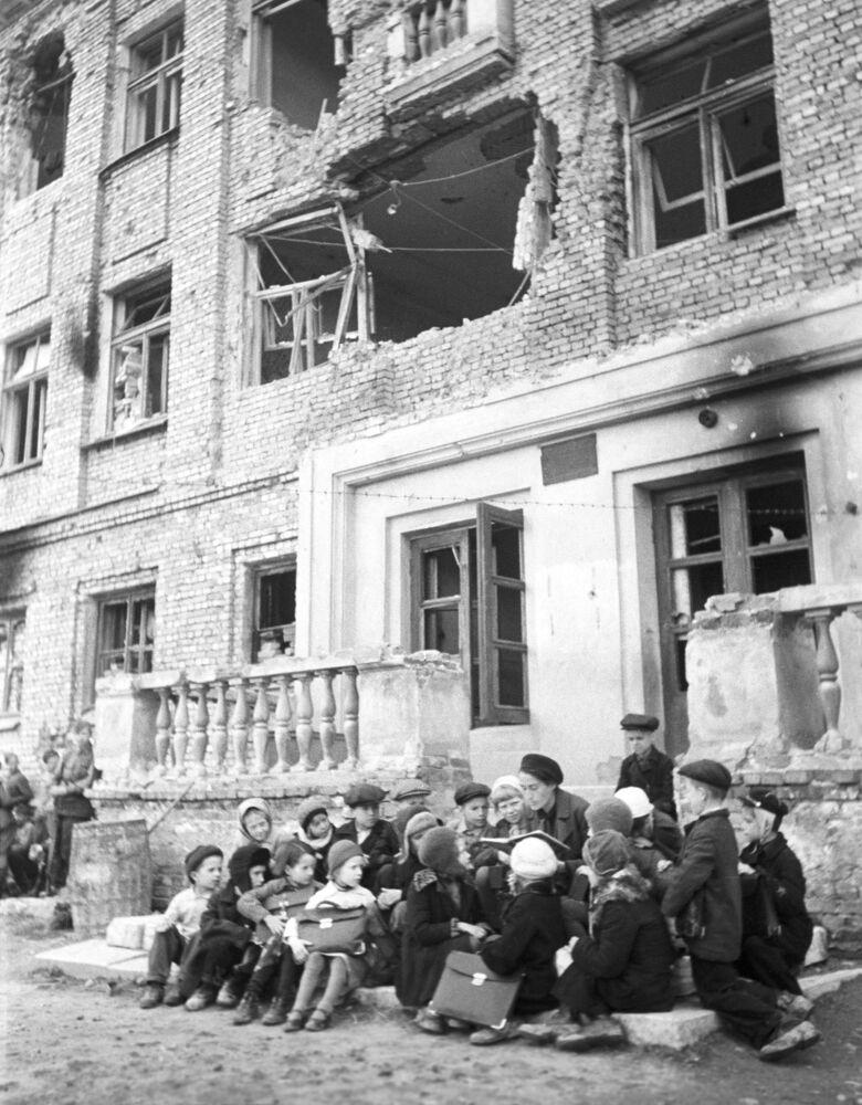Výuka na střední škole poblíž budovy, jež byla zničena německým bombardováním.