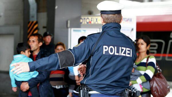 Německý policista a migranti. Ilustrační foto - Sputnik Česká republika