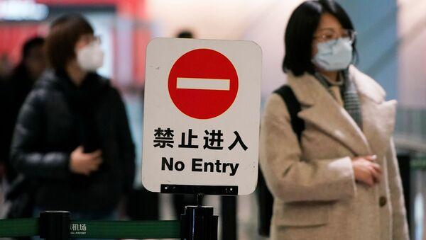 Cestující v masce na letišti v Šanghaji - Sputnik Česká republika