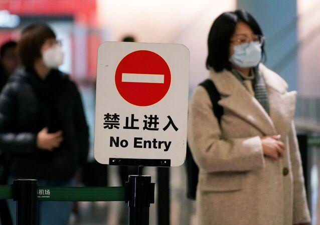 Cestující v masce na letišti v Šanghaji