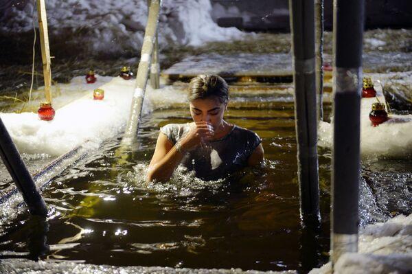 Žena během křestního koupání v Jekatěrinburgu, Rusko - Sputnik Česká republika