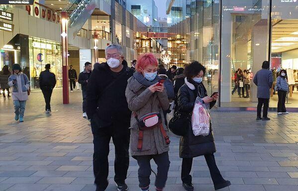 Kolemjdoucí v ochranných maskách na ulici v Pekingu - Sputnik Česká republika