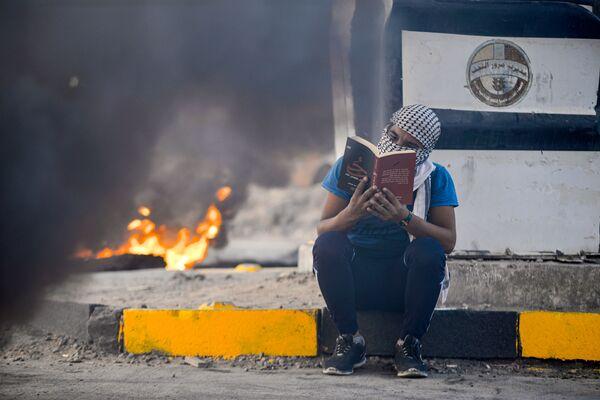 Protivládní protestant čte román uprostřed hořících pneumatik, Irák - Sputnik Česká republika