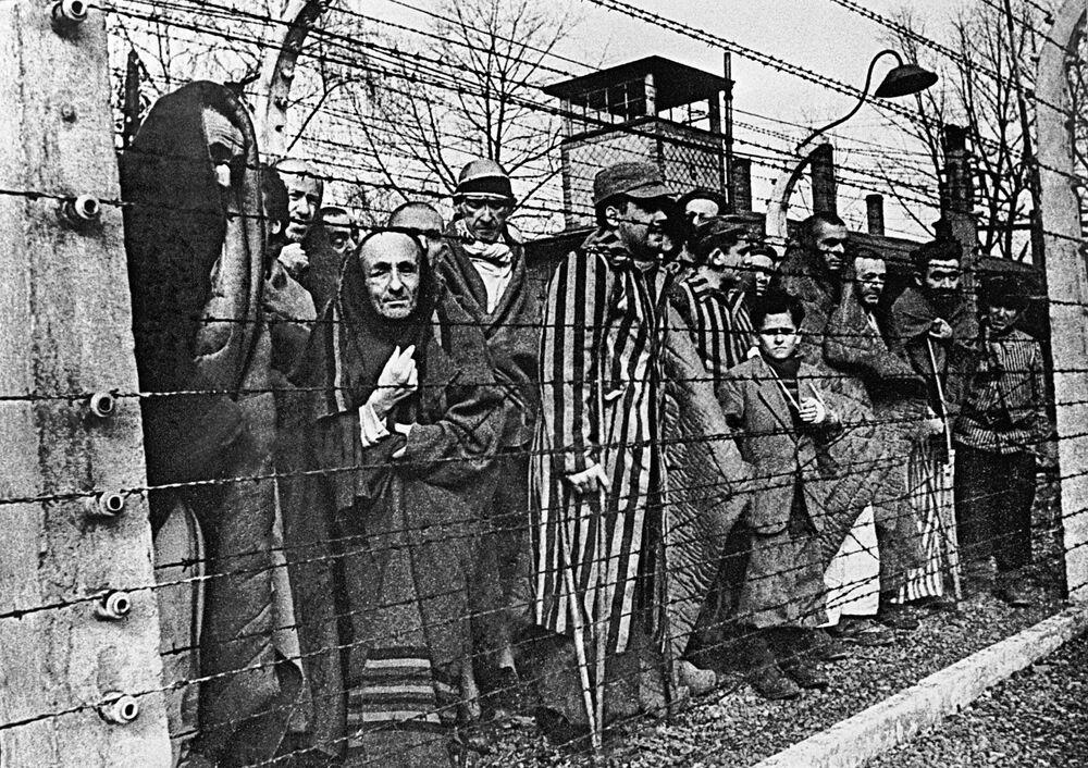 Vězni koncentračního tábora Osvětim se dívají do objektivu zpoza ostnatého drátu