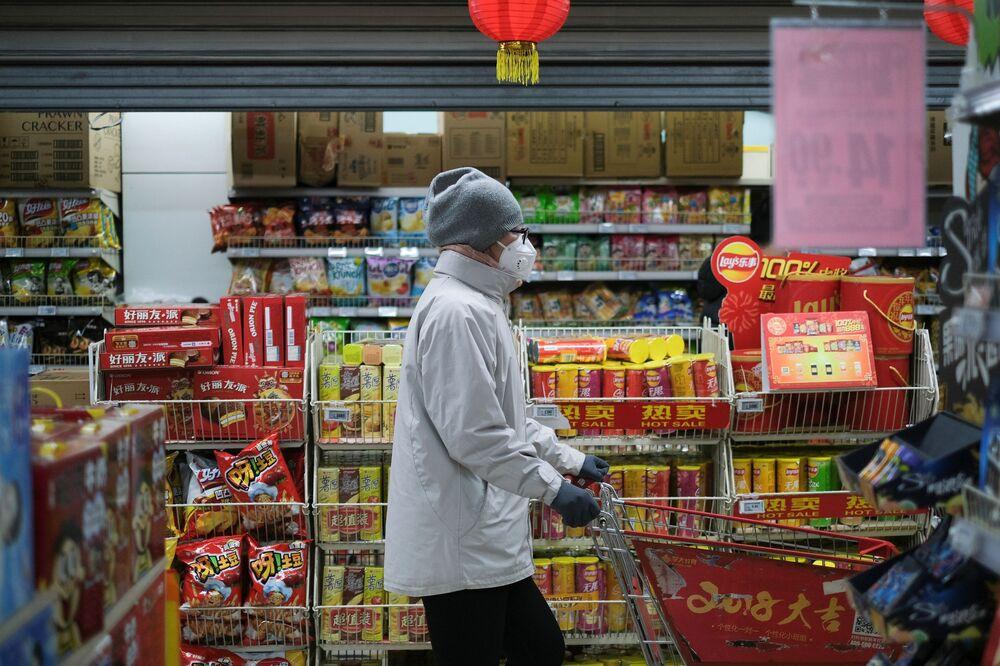 Žena v roušce v čínském obchodě