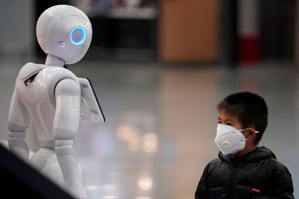 Chlapec v roušce se dívá na robota na mezinárodním letišti Šanghaj Pchu-tung