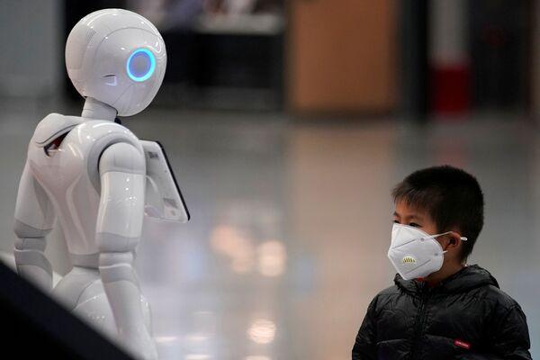 Chlapec v roušce se dívá na robota na mezinárodním letišti Šanghaj Pchu-tung - Sputnik Česká republika