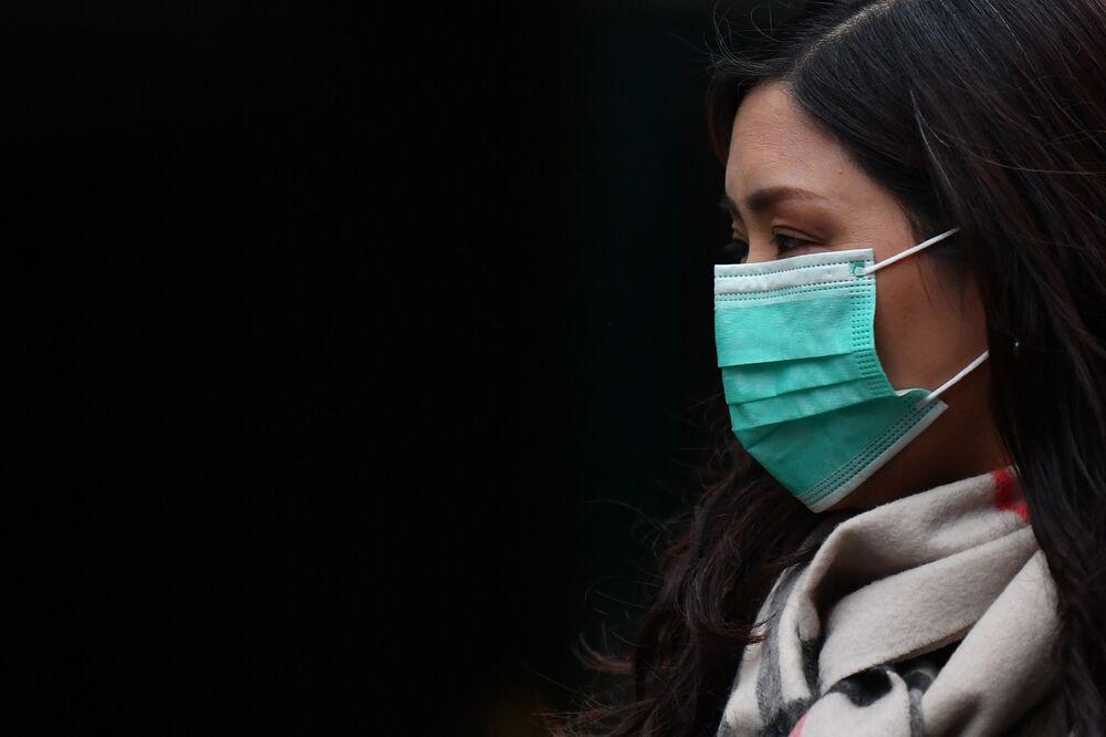 Žena v roušce v londýnské čínské čtvrti