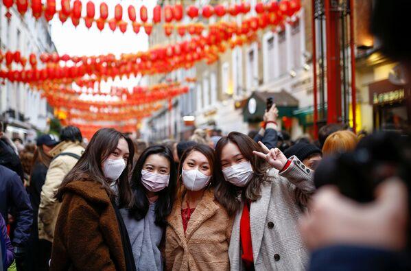 Lidé v rouškách oslavují příchod čínského Nového roku v Čínské čtvrti v Londýně - Sputnik Česká republika