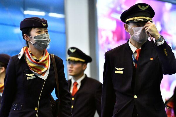 Posádka letadla v rouškách, která dorazila z Číny do Vancouveru - Sputnik Česká republika