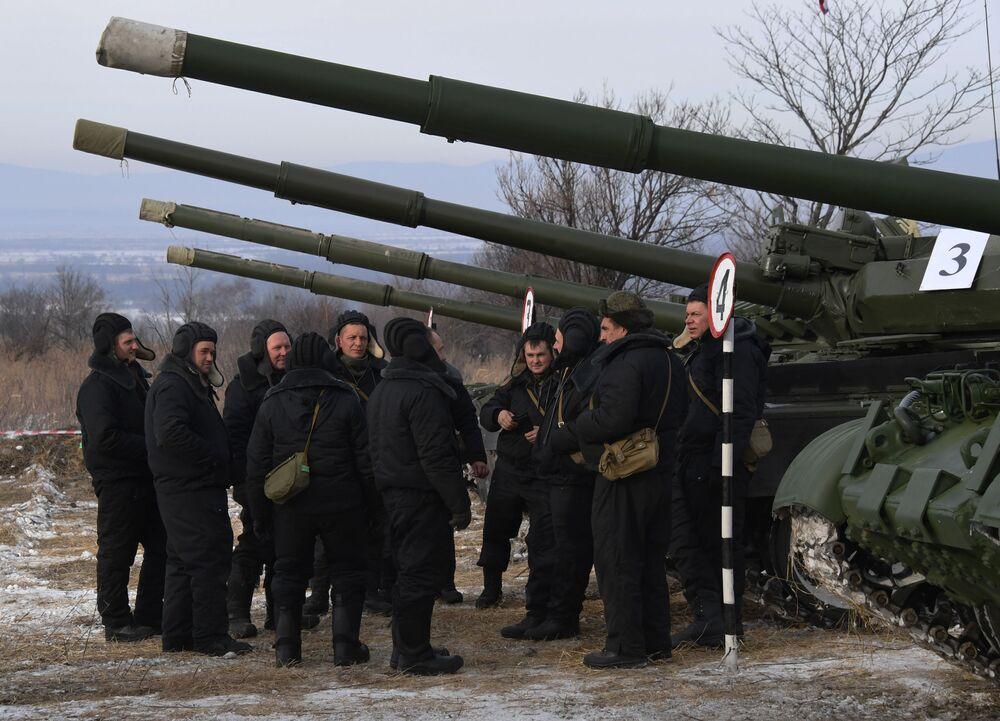 Ruští vojáci stojí před historickými tanky