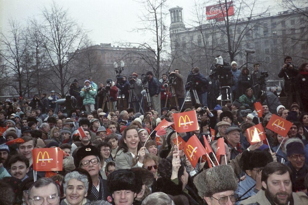 Pohled na Puškinovo náměstí v Moskvě před budovou první restaurace McDonald's v Rusku. Lidé mávají rudými vlajkami.