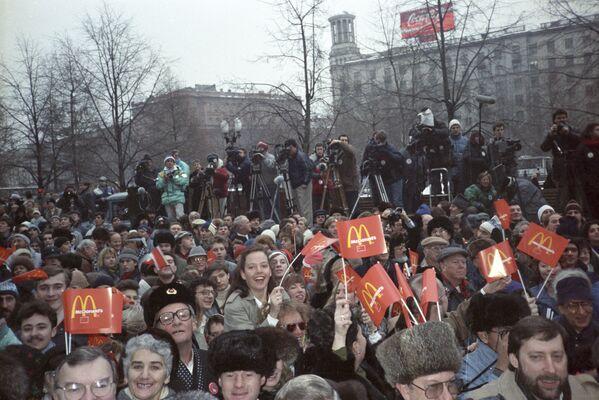 Pohled na Puškinovo náměstí v Moskvě před budovou první restaurace McDonald's v Rusku. Lidé mávají rudými vlajkami. - Sputnik Česká republika